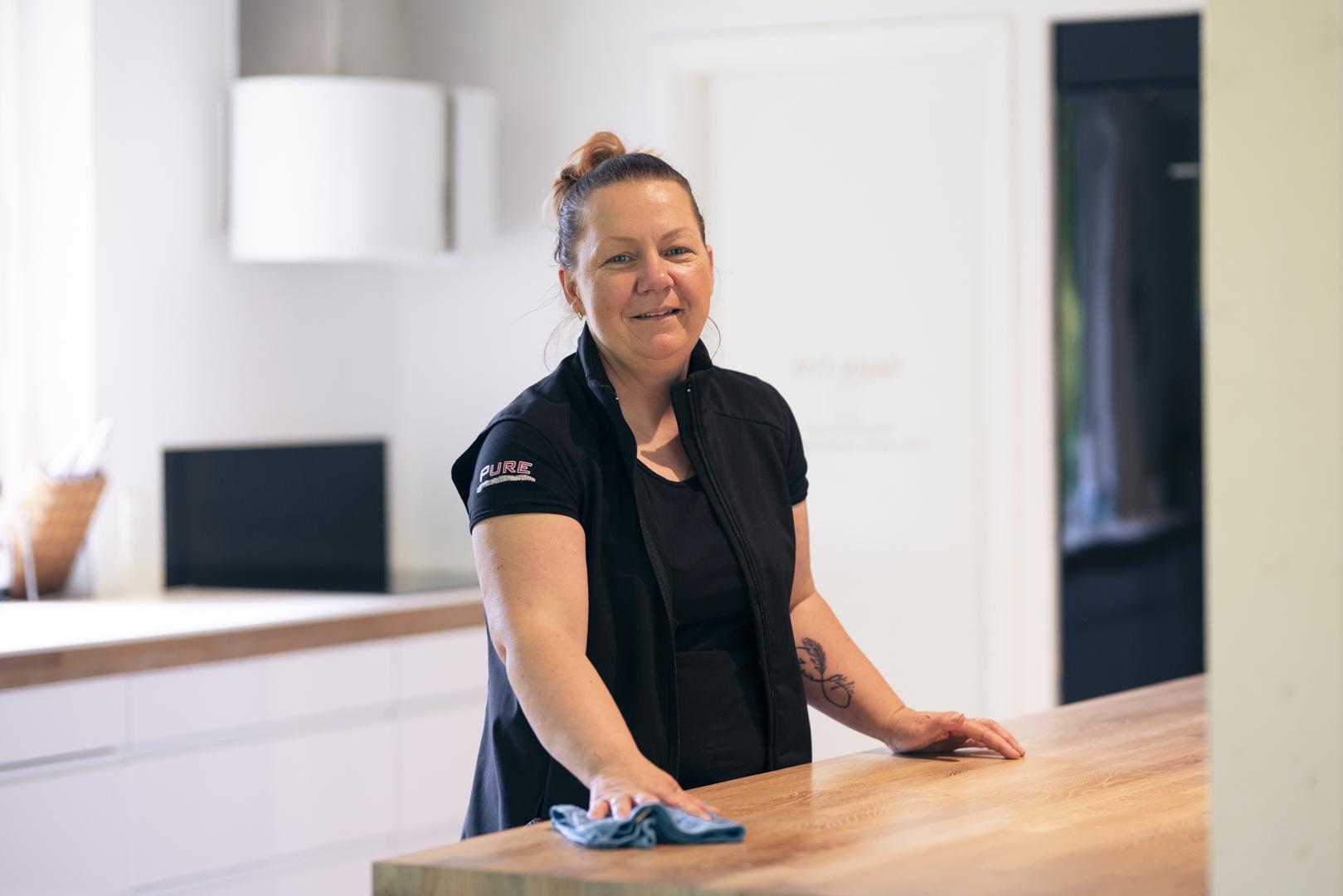 Kvinde fra rengøringsfirma tørrer bord af