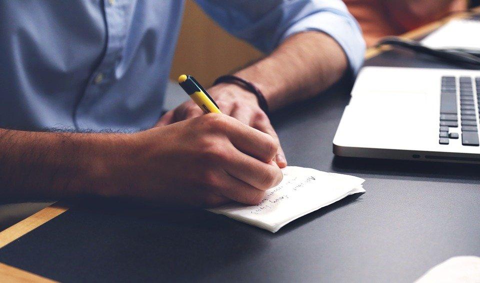 Mand ved laptop skriver i notesbog